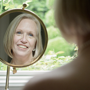 woman looking in mirror after facelift