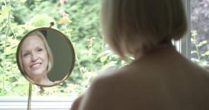 woman looking in mirror facial